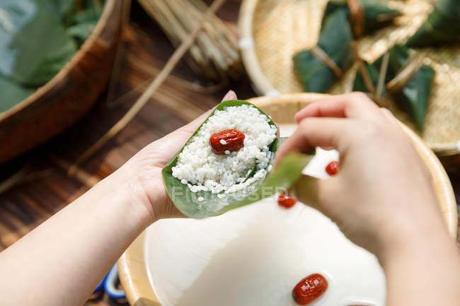 Abgeschnittene Aufnahme einer Frau bei der Zubereitung eines traditionellen chinesischen Reisgerichts zongzi — Stockfoto