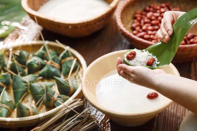 AbgeschnittenSchuss von Frau Vorbereitung traditionellen chinesischen Reis Gericht Zongzi — Stockfoto