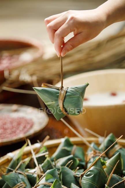 Teilansicht der Frau Kochen traditionellen chinesischen Gericht Zongzi — Stockfoto