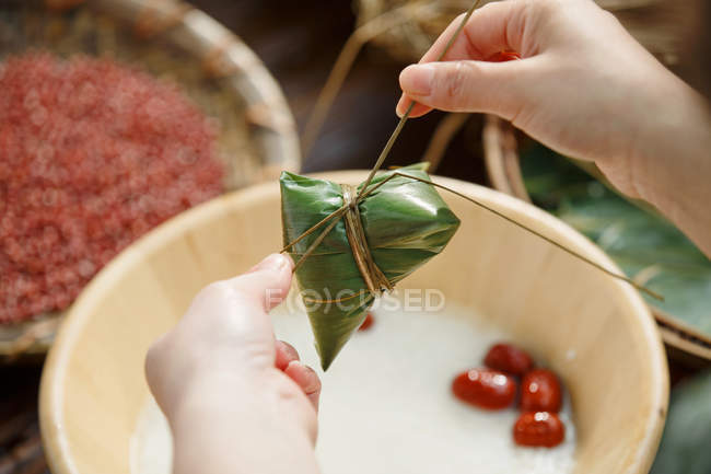 Close-up partial view of woman making traditional chinese dish zongzi — Stock Photo