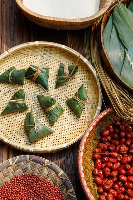 Vue rapprochée des ingrédients pour les zongzi et ingrédients chinois traditionnels enveloppés — Photo de stock