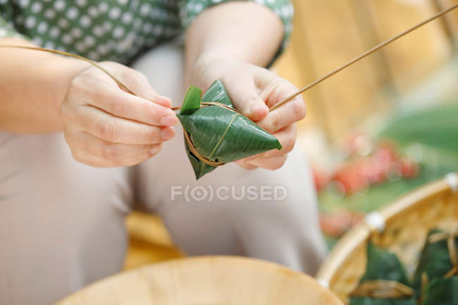 Nahaufnahme Teilansicht der Frau, die traditionelle chinesische Gericht Zongzi — Stockfoto