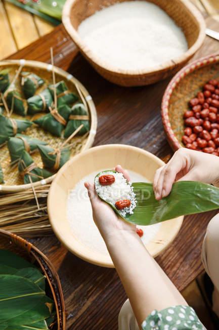 Abgeschnittene Aufnahme einer Frau mittleren Alters, die traditionelles chinesisches Gericht zongzi zubereitet — Stockfoto