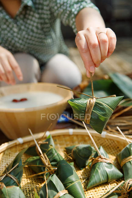 Close-up partial view of middle-aged woman making zongzi — Stock Photo