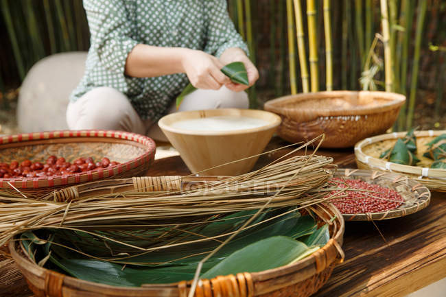 Partial view of middle-aged woman making zongzi — Stock Photo