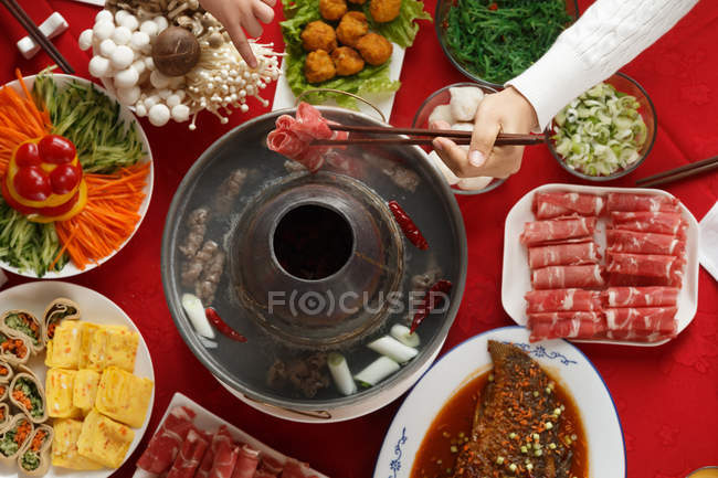 Cropped shot of people holding chopsticks and eating delicious hot pot meal — Stock Photo