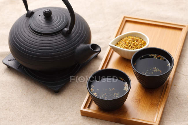 High angle view of black ceramic teapot and cups of tea on wooden tray — Stock Photo
