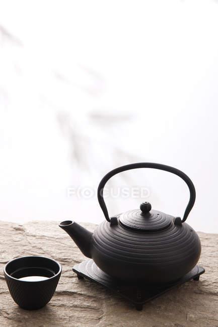 Крупний план огляду керамічного чайника і чашки на кам'яну поверхню на білому — стокове фото