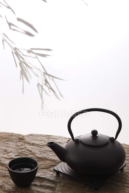 Close-up view of ceramic teapot and cup on stone surface on white — Stock Photo