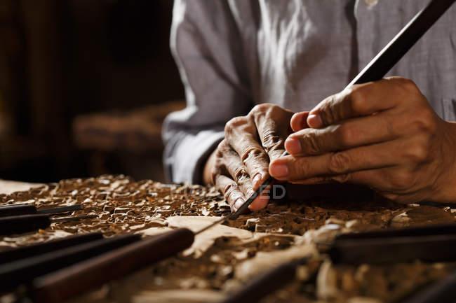 Colpo ritagliato dell'uomo durante l'incisione della lavorazione del legno, arte e artigianato tradizionale cinese — Foto stock