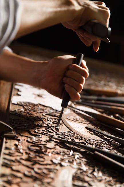 Vue partielle de plan rapproché des mains masculines pendant la gravure de travail du bois à l'atelier — Photo de stock