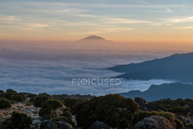 Amazing mountain landscape with scenic mountains covered with clouds during sunrise — стокове фото