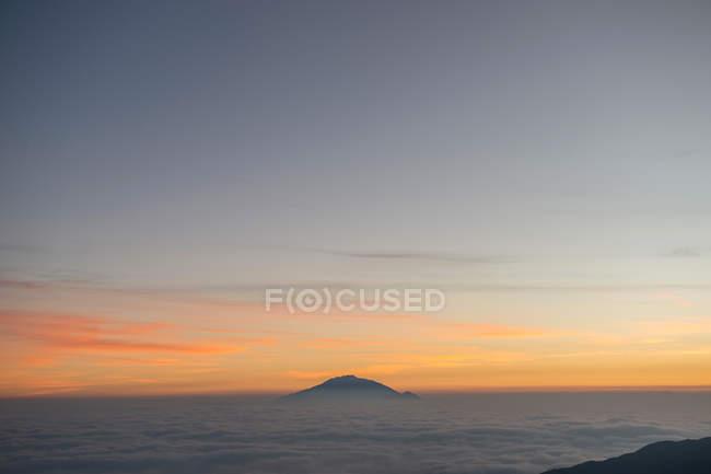 Vista aérea del majestuoso pico montañoso en las nubes durante el amanecer escénico. - foto de stock