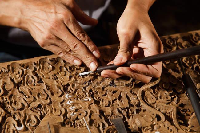 Visão parcial das mãos masculinas durante a gravura em madeira na oficina — Fotografia de Stock