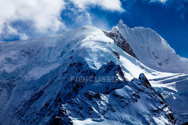 Дивовижний краєвид з засніженими горами і хмарами в синьому небі. — стокове фото