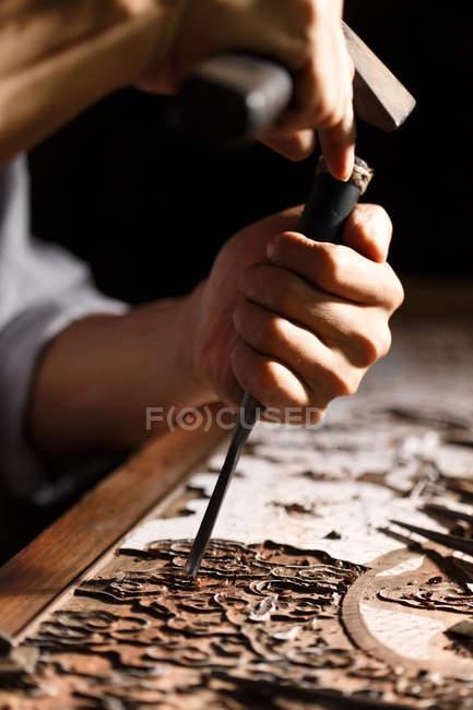 Vue partielle de l'homme pendant la gravure de travail du bois à l'atelier — Photo de stock