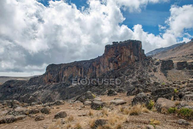 Paisagem incrível com montanhas rochosas e nuvens brancas no céu azul — Fotografia de Stock