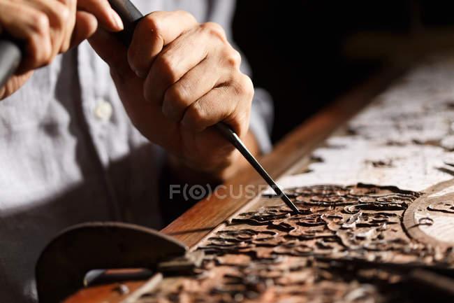 Vue partielle de plan rapproché de l'homme asiatique pendant la gravure de travail du bois à l'atelier — Photo de stock