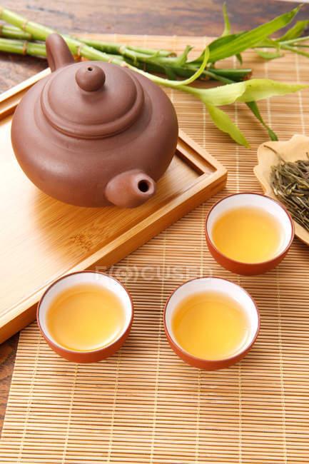 Високий кут зору коричневого чайника і чашки на бамбуковому килимок — стокове фото