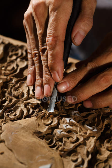 Cropped shot of man during woodworking engraving, traditional chinese art and craft — Stock Photo