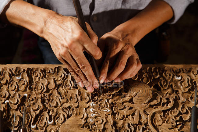 Cropped shot of asian man during woodworking engraving at workshop — Photo de stock