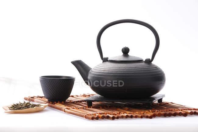 Théière en céramique noire et tasse de thé sur le fond blanc — Photo de stock