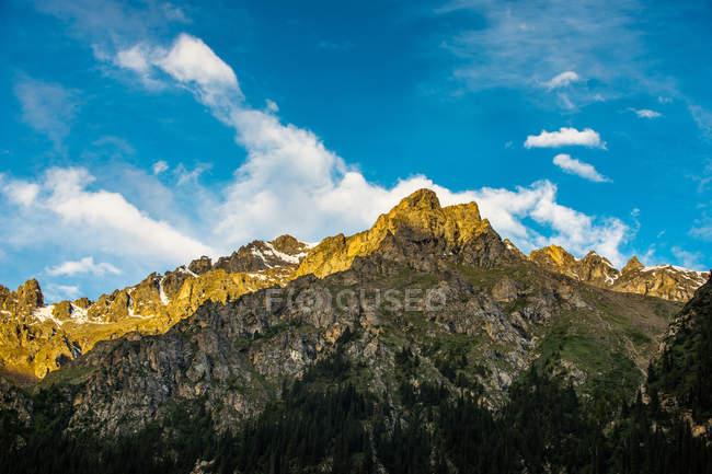 Increíble paisaje de montaña con montañas rocosas y nubes blancas en el cielo azul - foto de stock