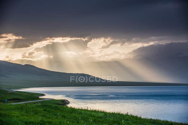 Beau paysage avec des montagnes pittoresques couvertes de végétation verte, plan d'eau et ciel nuageux — Photo de stock