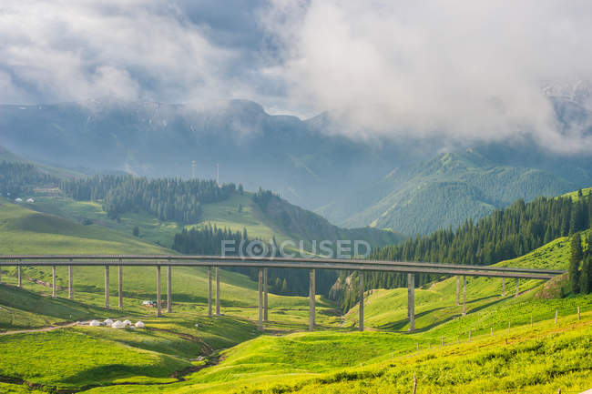 High angle view of bridge and beautiful mountains covered with lush green vegetation — Stock Photo