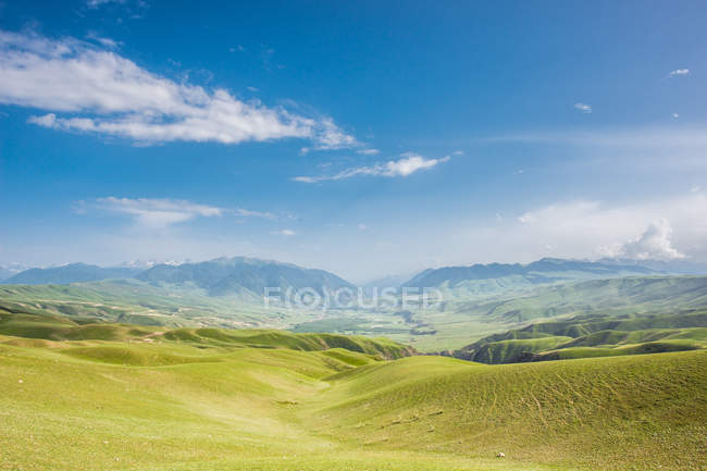 Amazing mountain landscape with green hills and blue sky at sunny day — стокове фото