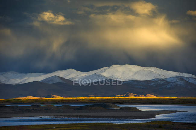 Amazing mountain landscape with dramatic cloudy sky above scenic snow-covered mountains — Stock Photo