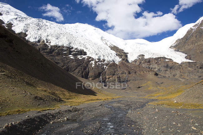 Beautiful landscape with river in valley and snow-covered rocky mountains at sunny day — Stock Photo