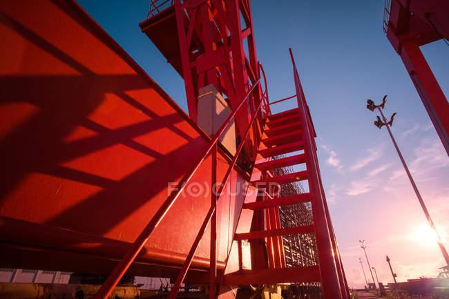 Vue à angle bas de la grue portique industrielle rouge au lever du soleil — Photo de stock