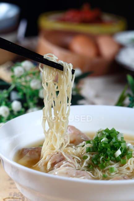Nahaufnahme von Essstäbchen mit köstlichen Wonton-Nudeln — Stockfoto