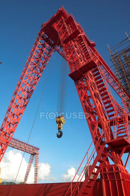 Vue à angle bas de la grue portique industrielle rouge contre le ciel bleu — Photo de stock
