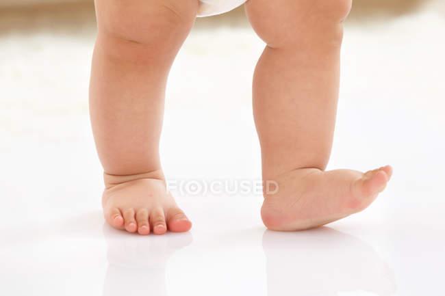 Niedriger Abschnitt des entzückenden barfüßigen Babys, das auf weißem Boden geht — Stockfoto