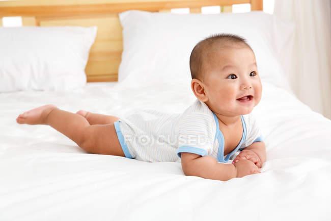 На ліжку лежить милий підборіддя. — стокове фото