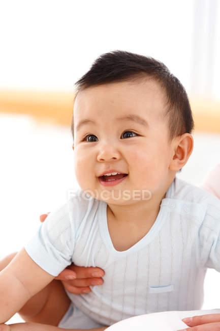 Abgeschnittene Aufnahme von Mutter, die entzückend glücklichen kleinen Jungen trägt — Stockfoto