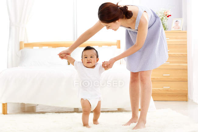 Молода мати вчила гарного малюка ходити додому. — стокове фото