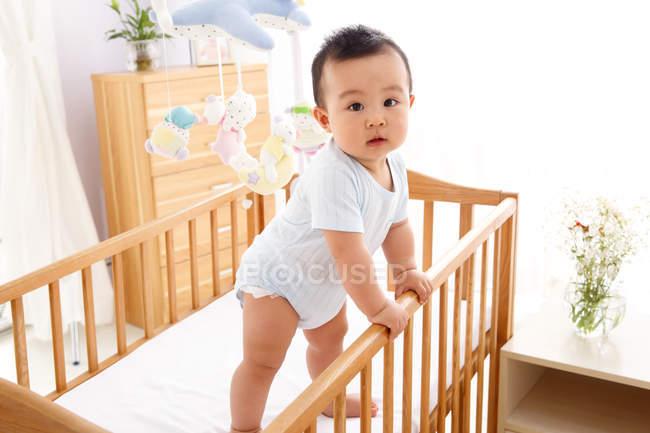 Милий азійський хлопчик, що стоїть на колисці і дивиться на камеру. — стокове фото