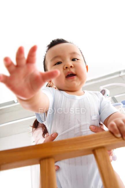 Низкий угол обзора очаровательного азиатского ребенка, стоящего в кроватке и смотрящего в камеру — стоковое фото