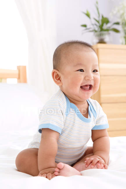 Bonito feliz asiático bebê menino sentado no cama — Fotografia de Stock