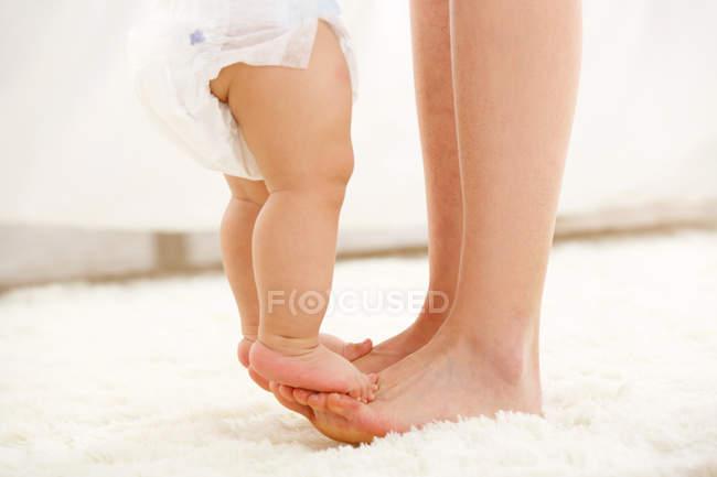 Crochet de la mère et du bébé dans la couche debout sur le tapis blanc — Photo de stock