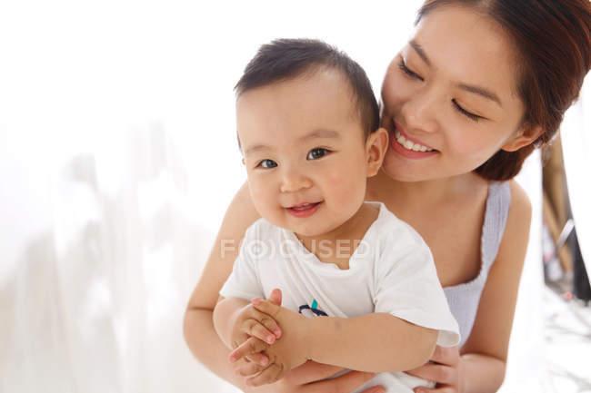 Heureuse jeune mère étreignant adorable petit bébé à la maison — Photo de stock