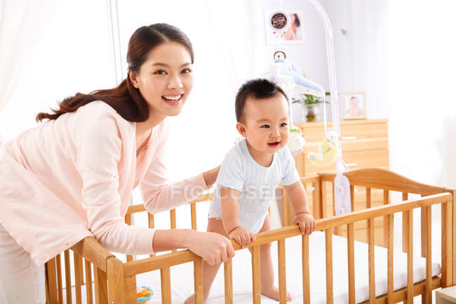 Happy young mother playing with adorable little baby standing in crib — Stock Photo