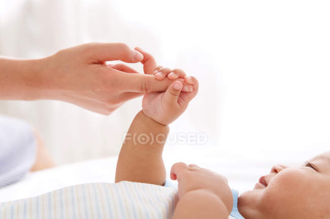 Cropped shot of adorable little baby holding finger of mother — Stock Photo
