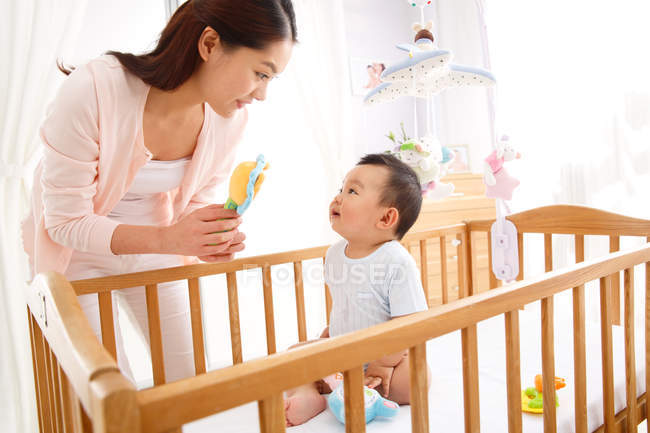 Happy young mother playing with adorable little baby sitting in crib — Stock Photo