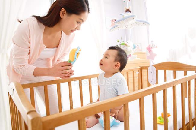 Heureuse jeune mère jouer avec adorable petit bébé assis dans la crèche — Photo de stock