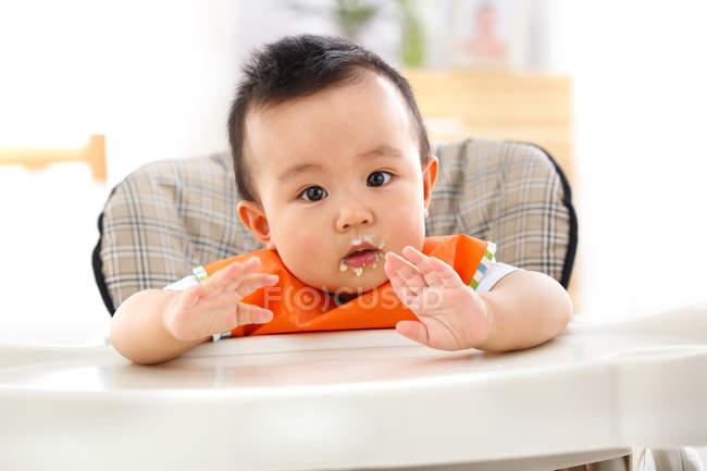 Симпатичный азиатский мальчик сидит в высоком кресле и смотрит в камеру — стоковое фото