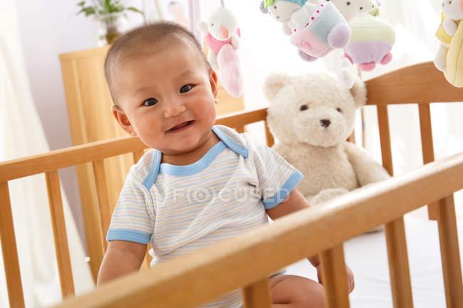 Adorabile bambino felice ragazzo con orsacchiotto in culla — Foto stock